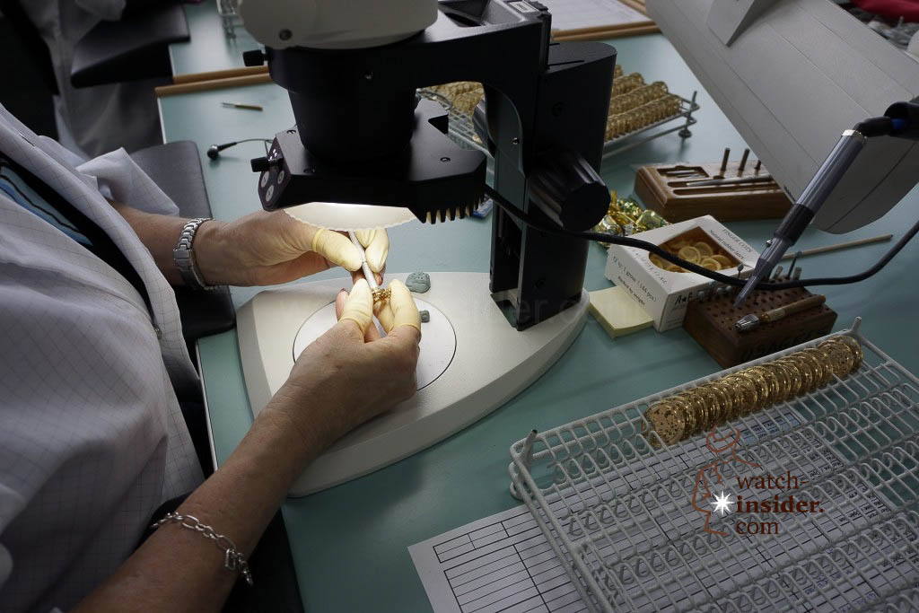 … Skilled hands trim the main plate by removing burrs from it …